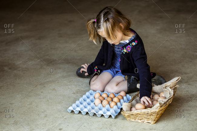 Girl kneeling on floor, placing eggs in a basket.