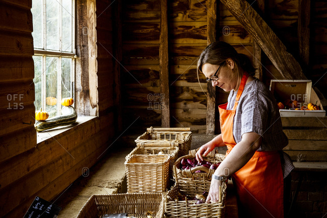 Woman wearing apron standing in farm shop, arranging baskets with vegetables.