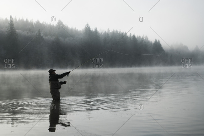 Silhouette of fisherman fly fishing for salmon and sea run cutthroat trout in Puget Sound near Olympia, Washington USA.