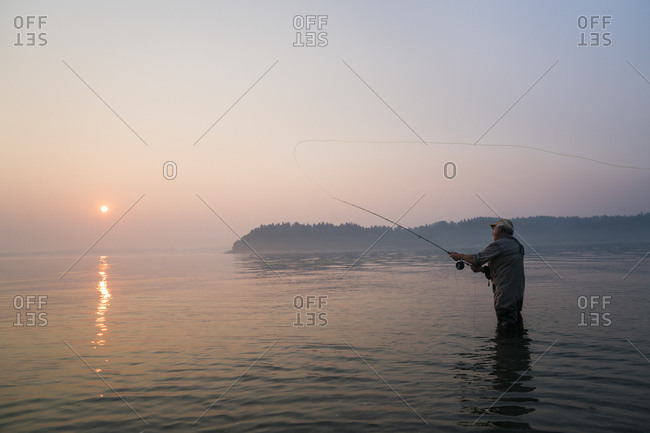 Senior Caucasian male fly fishing for salmon and sea run cutthroat trout in Puget Sound near Port Orchard, Washington USA