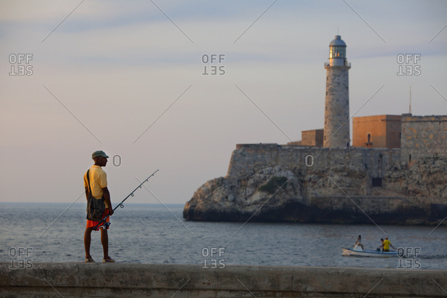 December 18, 2018: A fisherman standing on the railing on the Malecon at the entrance to the harbor in Havana, Cuba.