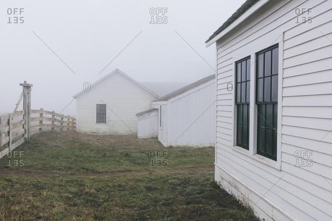 Outbuildings and barn on farm with dense fog, Historic Pierce Point Ranch, Point Reyes National Seashore, California, USA.