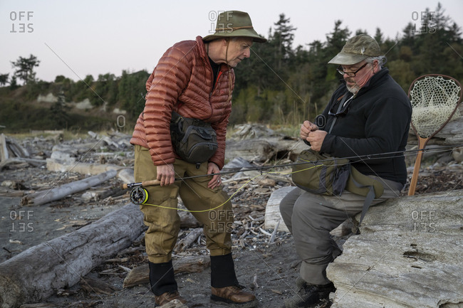 A male fly fisherman watches his guide work putting on a new fly to try for salmon or trout at a salt water beach.