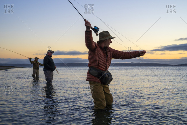 Two fly fishermen cast for searun coastal cutthroat trout and salmon with their guide standing between them on a salt water beach on a beach on the west coast of the USA