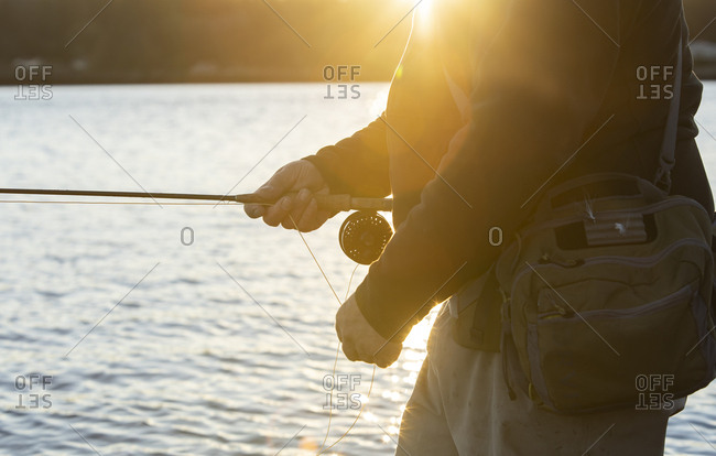 A closeup view of a the hands of a fly fisherman retrieving his line from a cast he made into salt water.