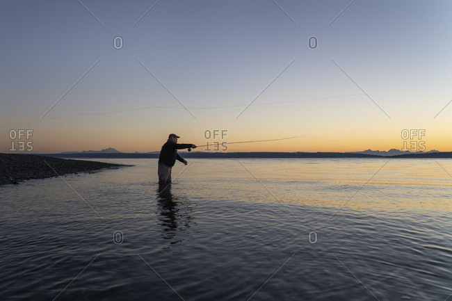 A silhouette view of a fly fisherman casting for salmon and searun coastal cutthroat trout from a salt water beach at a beach on the north west coastline of the USA.