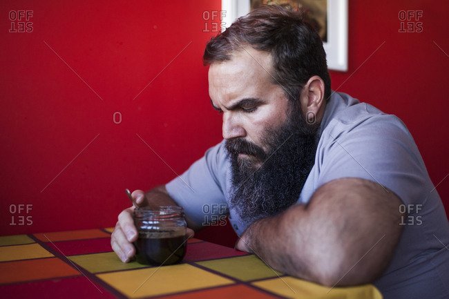 Bearded man drinking craft coffee at his kitchen table