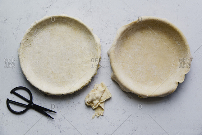 Raw uncooked pie crust in baking pan for two pies on concrete background
