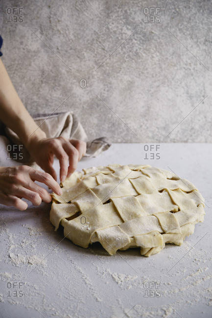 Uncooked apple pie with a wide lattice on top. Female hands making Concrete background, preparation process.