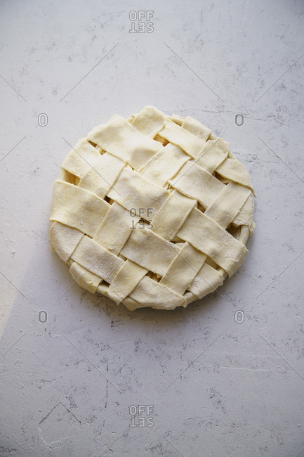 Uncooked apple pie with a wide lattice on top. Concrete background, preparation process.