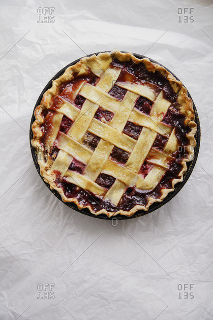 Berry pie with a lattice decoration on white background