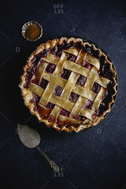 Berry pie with a lattice decoration on dark background with metallic spatula for serving