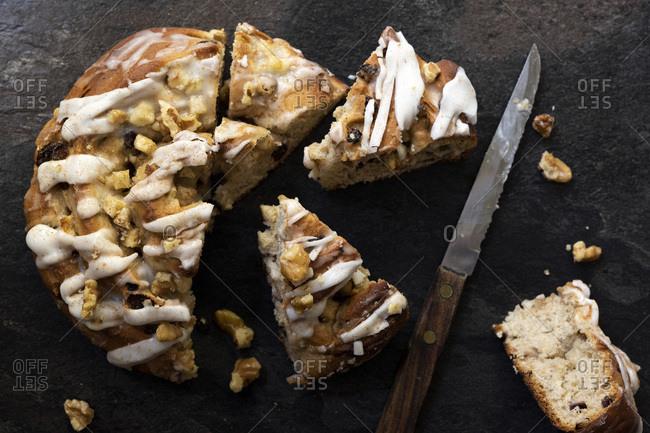 Apple, walnut and cinnamon bun cut into pieces with a knife.
