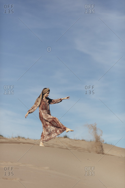 Model dressed as nomadic woman kicking sand in the desert