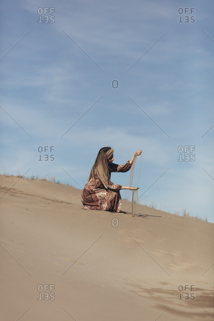 Model dressed as nomadic woman weighing sand in the desert
