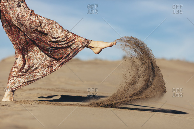 Close-up of woman kicking sand in the desert