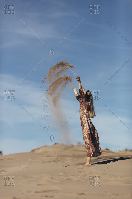 Model dressed as nomadic woman throwing sand in the desert