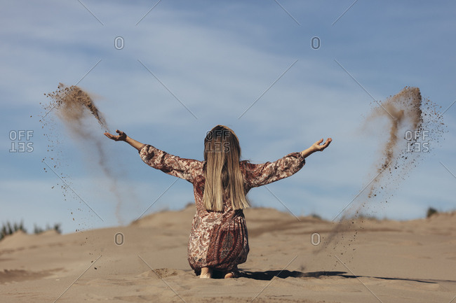 Model dressed as nomadic woman crouching down and throwing sand in the desert