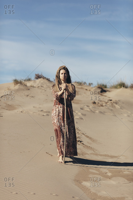 Model dressed as nomadic woman standing in the desert