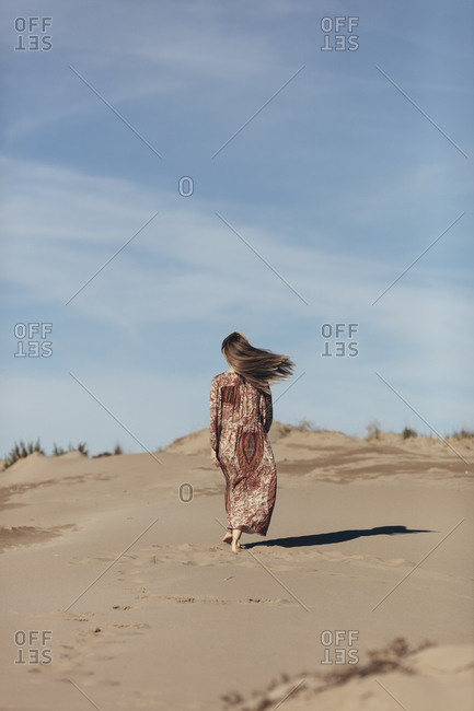 Model dressed as nomadic woman walking into the desert