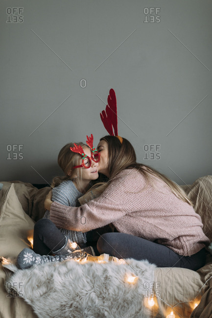 Mom kissing daughter on the cheek during christmas