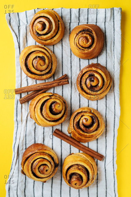 Cinnamon rolls and cinnamon sticks on striped towel