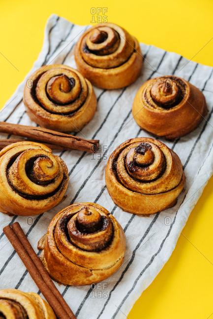 Cinnamon rolls and cinnamon sticks on striped towel on yellow counter