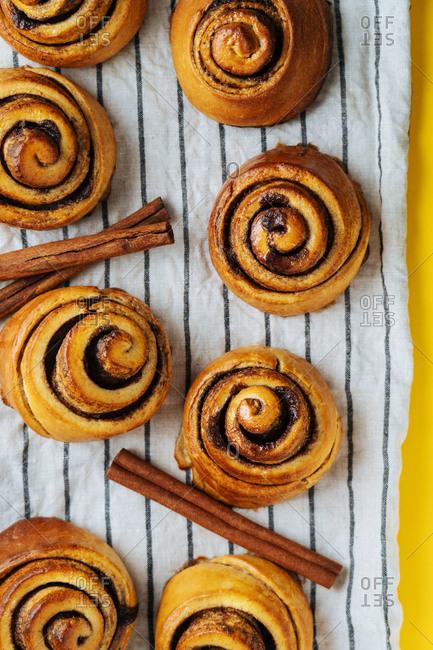 Cinnamon rolls and cinnamon sticks on a towel on yellow counter