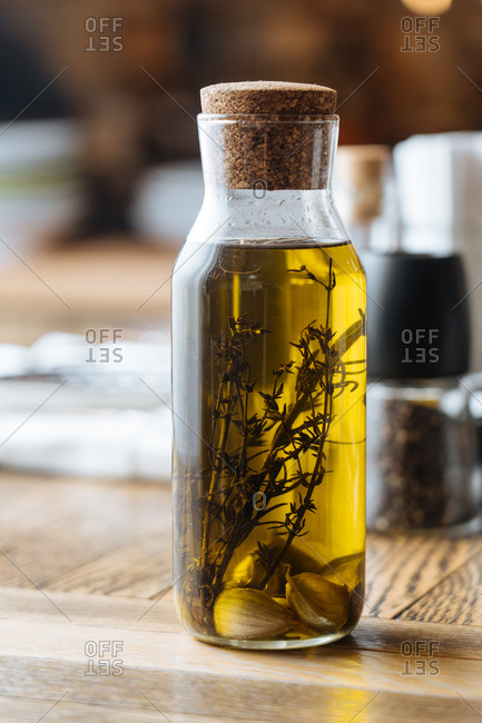 Herbs in a glass jar with olive oil