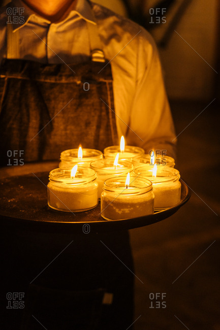 Person wearing apron holding tray of candles