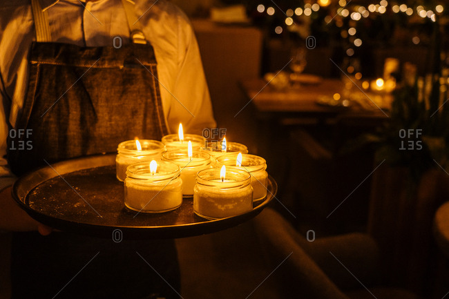 Man wearing apron holding tray of candles