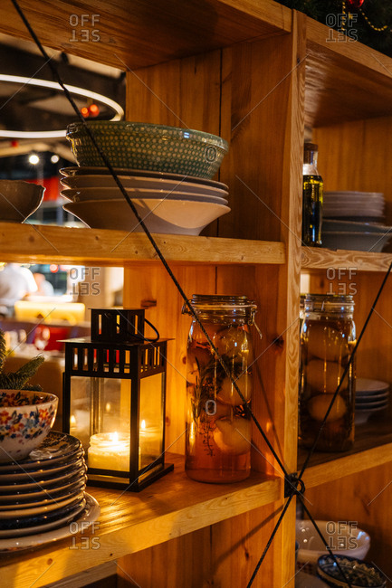 Candle in a lantern on a shelf with dishes