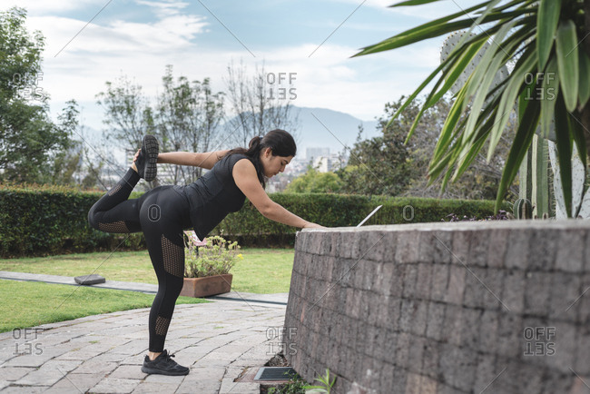 Young woman stretching leg before urban workout in garden