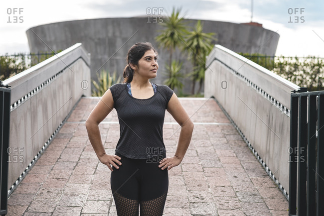 Latino woman portrait in sportswear with hands on hips looking away near footbridge in Mexico city