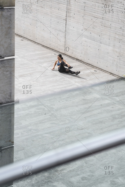 Young Latino woman in sportswear doing abdominal exercises on walkway in Mexico city