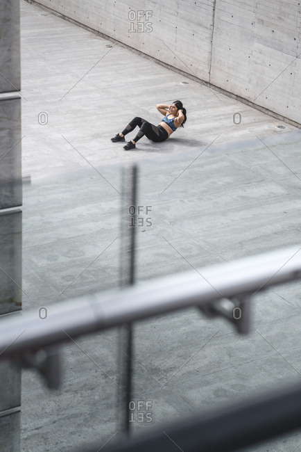 Young Latino woman in sportswear doing crunches on walkway in Mexico city