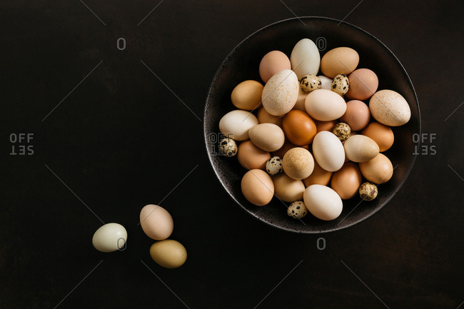 Variety of eggs on black background