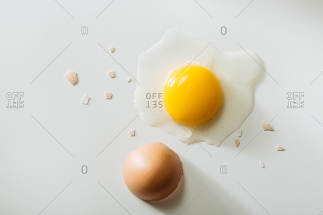 Egg cracked open on white background