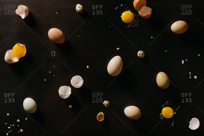 Variety of eggs cracked on dark background