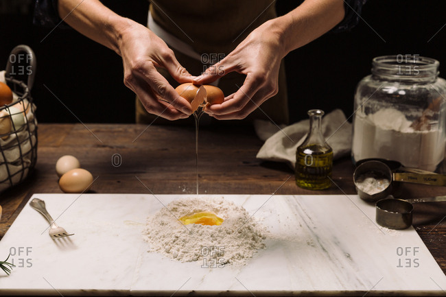 Chef cracking egg into flour on marble slab while cooking