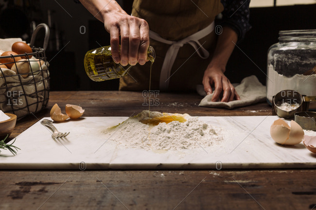 Chef sprinkling salt into egg and flour on marble slab while cooking