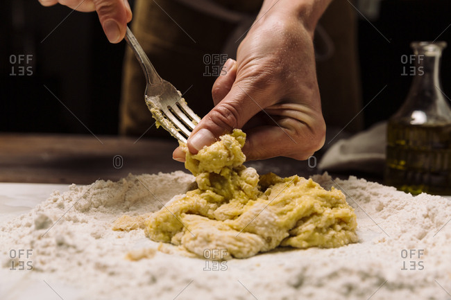 Chef stirring dough on marble slab while cooking