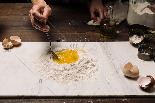 Chef stirring egg and flour on marble slab while cooking