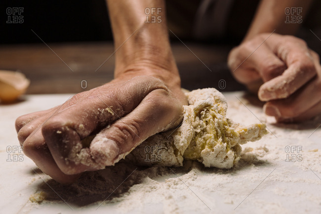 Chef kneading dough on marble slab while cooking