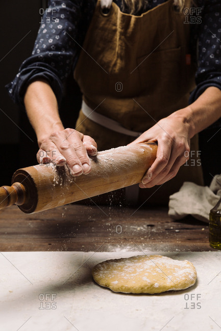 Chef putting flour onto rolling pin