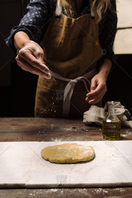 Chef sprinkling flour onto dough
