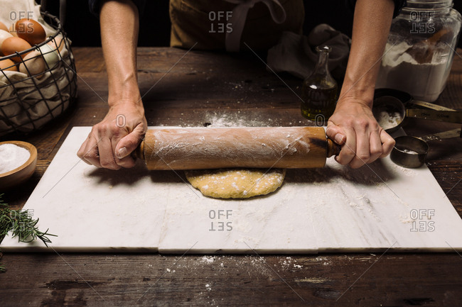Chef rolling dough with a rolling pin