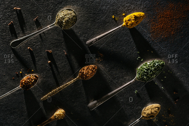 Various spices on spoons on dark background