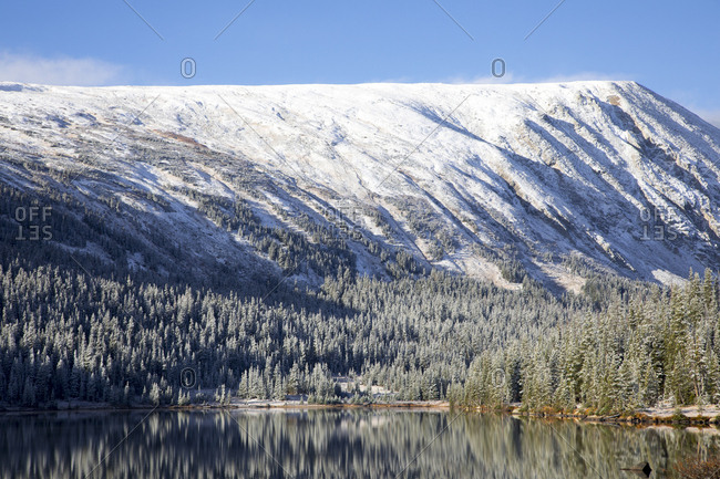 Beautiful snowy mountain and trees reflecting in lake