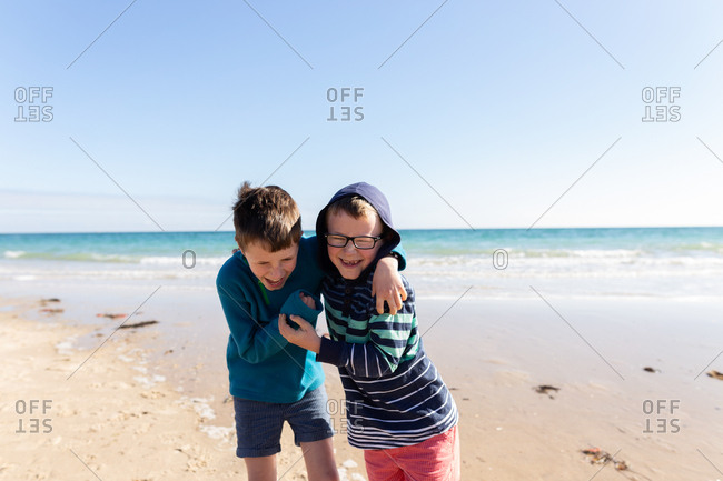 Two boys laughing with arms around each other on sandy beach
